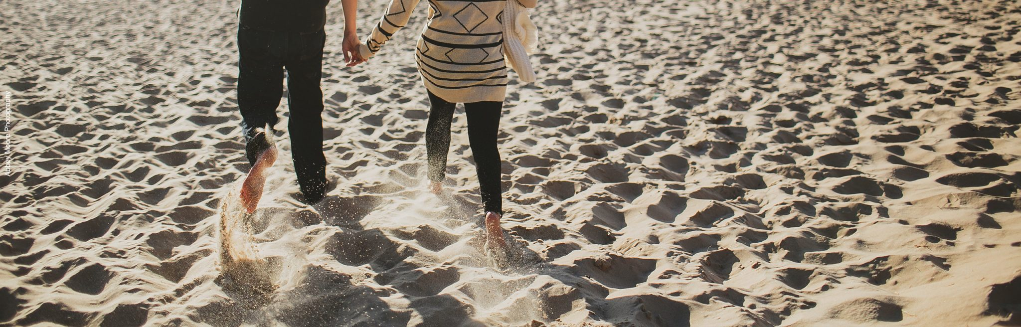 Couple-Running-Through-Sand-PageSlider-Recovered